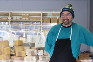 Mike wears a blue jumper, an apron and a bobble hat, and is standing in front of a display counter full of different cheeses.