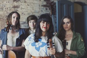 Singer Laura Cortese pictured in front of a brick wall and blue door, with three members of her band