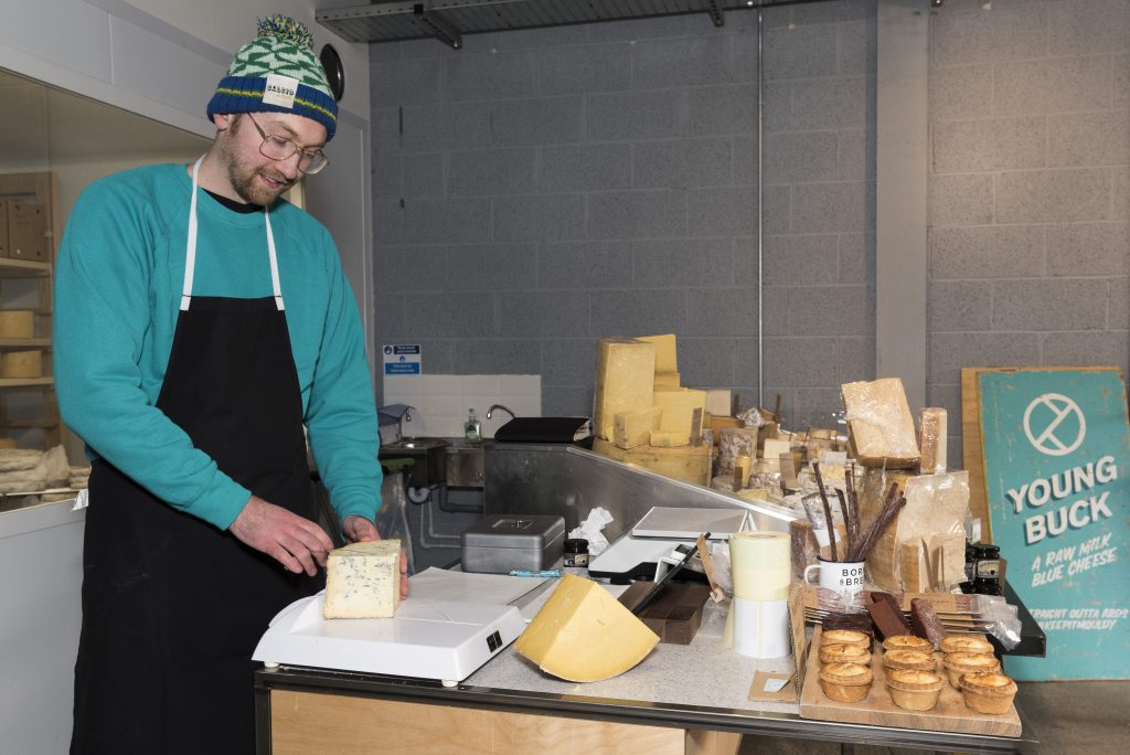 Mike Thomson cutting cheese using a wire on a cutting board
