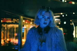 Woman in faux fur coat, under blue light.